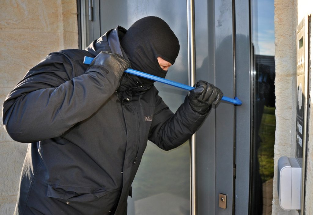 Zu sehen ist ein Einbrecher an einer Wohnungstür mit einem Brecheisen; Aufgenommen mit einer Überwachungskamera